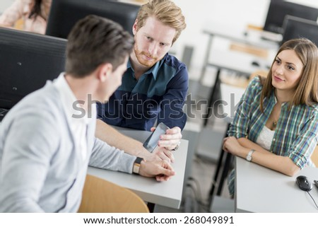 Young students talking in a classroom during break - stock photo