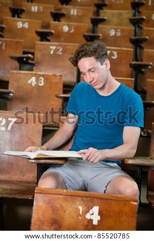 Young studious boy studying at university hall - stock photo