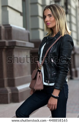 Young stylish and glamorous girl with stylish female leather bag outdoors. Fashionable and high style expensive female bag. Sales bag fashion concept