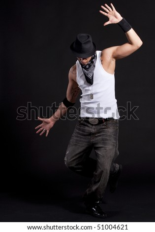 Young stylish asian dancer in front of black background moving to hip hop music.
