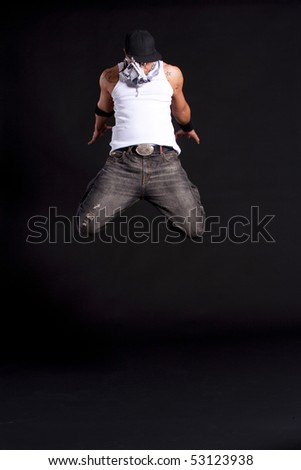 Young stylish asian dancer in front of black background moving to hip jop music. - stock photo