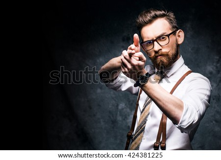 Young stylish bearded man in glasses aiming a finger gun
