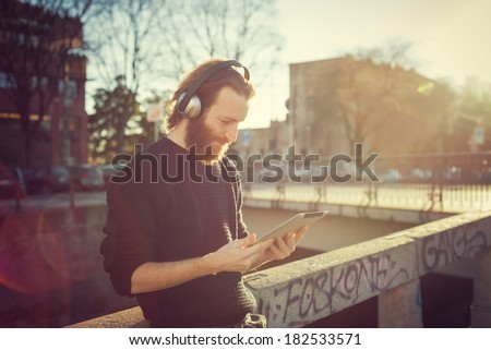 young stylish bearded man listening to music in the city - stock photo
