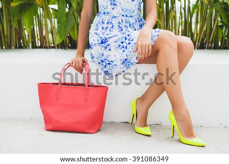 young stylish beautiful woman in blue printed dress, red bag, fashionable outfit, trendy apparel, sitting, yellow high heel shoes, accessories, close up legs, details - stock photo