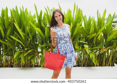 young stylish beautiful woman in blue printed dress, red bag, sunglasses, happy mood, fashionable outfit, trendy apparel, smiling, summer, accessories