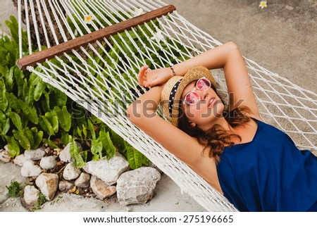 young stylish beautiful woman in pink sunglasses and straw hat blue dress laying in hammock at resort pool, smiling happy, enjoying summer day, vacation, relax, flowers - stock photo