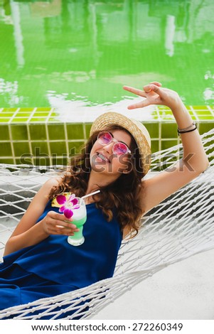 young stylish beautiful woman in pink sunglasses and straw hat with a tropical cocktail sitting in hammock at pool, smiling and happy, enjoying summer day, vacation, showing peace sign on her fingers - stock photo
