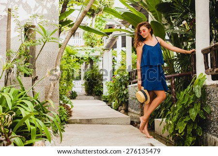 young stylish beautiful woman, pink sunglasses, holding straw hat, tropical resort hotel, walking, elegant and sexy, dreamy, thoughtful, sophisticated, relaxed mood  - stock photo