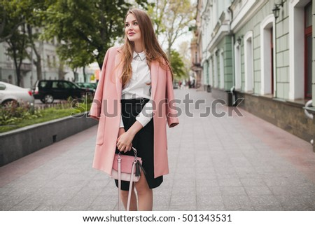 young stylish beautiful woman walking in street, wearing pink coat, purse, white shirt, black skirt, fashion outfit, autumn trend, smiling happy, accessories