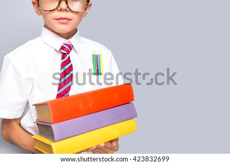 Young stylish boy with books, focus on face - stock photo