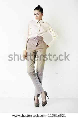 Young stylish brunette casual successful business woman in white blouse and pants isolated on white - stock photo