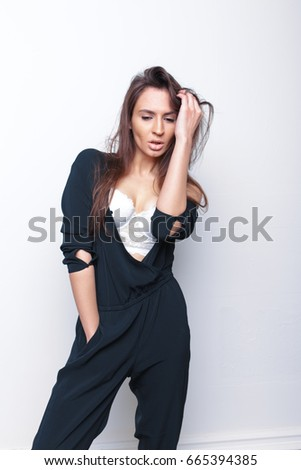 young stylish brunette girl in overalls. slim figure and clean skin. posing in a photo Studio. white background. emotional portraits. long hair and pouty lips.