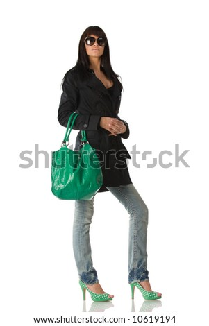 Young stylish brunette in sun glasses posing with green purse. Isolated over white - stock photo