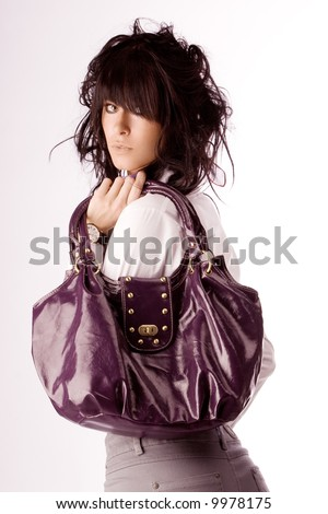Young stylish brunette posing with violet purse. Isolated over white - stock photo