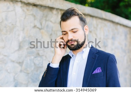 Young stylish business man talking on the phone over stoned wall outdoors