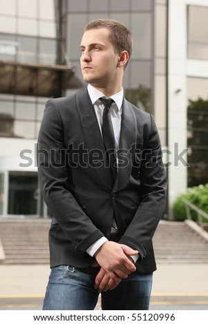 young stylish businessman against office building - stock photo