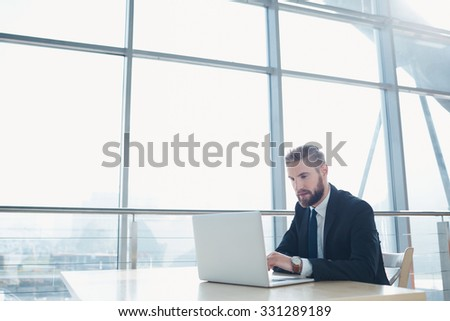 Young stylish businessman working at modern office with his laptop - stock photo
