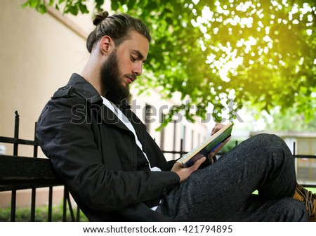 Young stylish Caucasian man reading a book outdoors. - stock photo