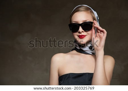 young stylish caucasian woman posing, over dark background, retro styling