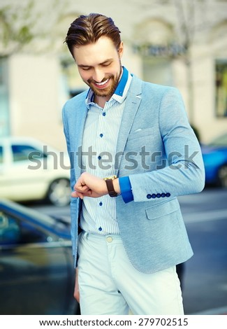 Young stylish confident happy handsome businessman model  in suit cloth lifestyle in the street look his watch - stock photo