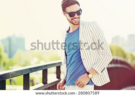 Young stylish confident happy handsome businessman model  in suit hipster cloth lifestyle in the street standing near wall - stock photo