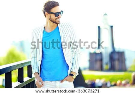 Young stylish confident happy handsome businessman model in suit hipster clothes walking in the street in sunglasses - stock photo