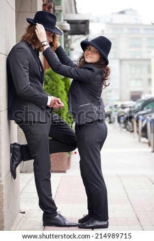 Young stylish couple in black hats posing on the street - stock photo