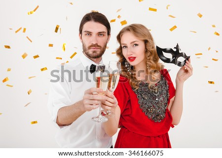 young stylish couple in love drinking champagne, celebrating new year, wearing red dress, fashion jewelry, bow tie, happy disco party, holding glasses and toasting, cheerful, having fun, cool outfit - stock photo