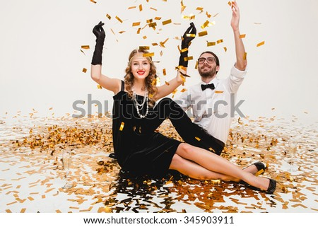 young stylish couple in love on white background sitting on floor, throwing golden confetti, celebrating new year, wearing black dress, happy carnival disco party, having fun, smiling - stock photo
