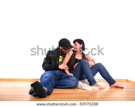 Young stylish couple sitting on the floor of their new home! Pure white wall leaves big copyspace. - stock photo