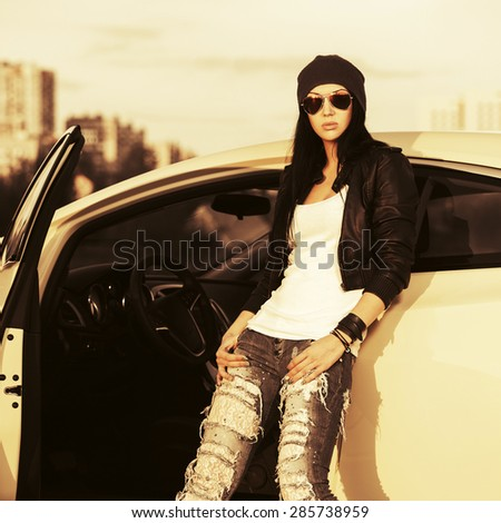 Young stylish fashion woman in sunglasses by her car outdoor - stock photo