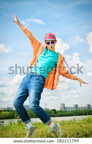 Young stylish girl dancing hip-hop outdoors. Youth fashion. Hip-hop style. - stock photo