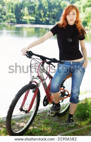 Young stylish girl in blue jeans with bicycle outdoors against blurred lake and green