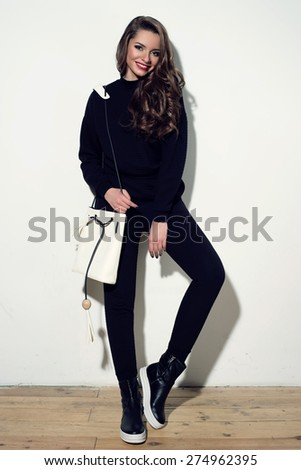 Young stylish girl posing in black costume trousers and pullover and black boots with white handbag in simple interior against white wall. Happy cheerful smiling woman. - stock photo