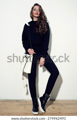 Young stylish girl posing in black costume trousers and pullover and black boots with white handbag in simple interior against white wall