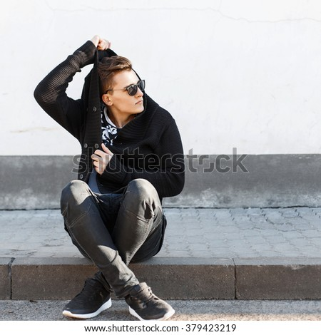Young stylish guy in sunglasses sitting on the curb on the background of a white wall. - stock photo