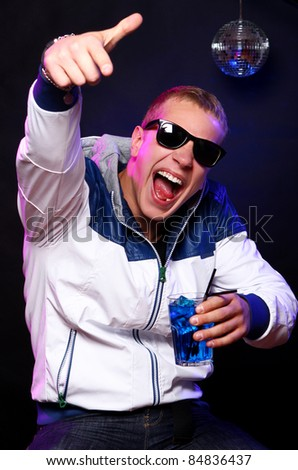 Young stylish guy with a blue cocktail in the nightclub - stock photo