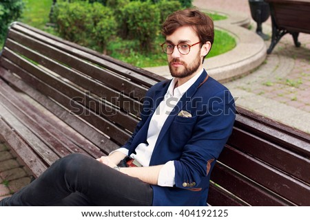 Young stylish handsome bearded hipster man sitting outdoor on the bench in park in glasses and blue suit  - stock photo