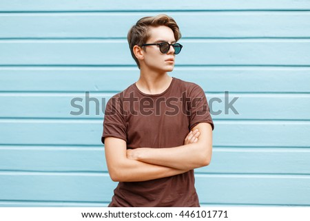 Young stylish handsome man is posing next to a bright blue wall. - stock photo