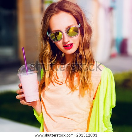 Young stylish hipster blonde  girl n in cool sunglasses with cocktail posing outdoor against bright color urban background . Wearing neon outfit and jeans.