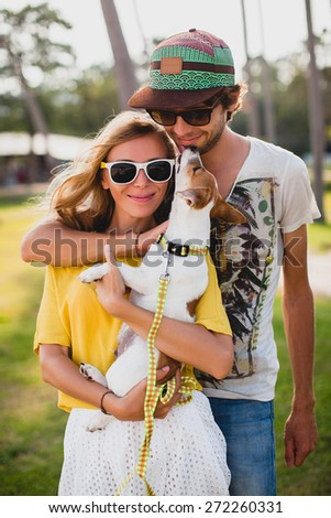 young stylish hipster couple in love holding a dog at the tropical park, smiling and having fun during their vacation, wearing sunglasses, cap, yellow and printed shirt, romance - stock photo