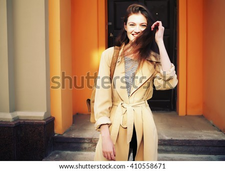 Young stylish hipster girl wearing modern trench coat walking in urban city smiling happy. Caucasian female model in her 20s. - stock photo