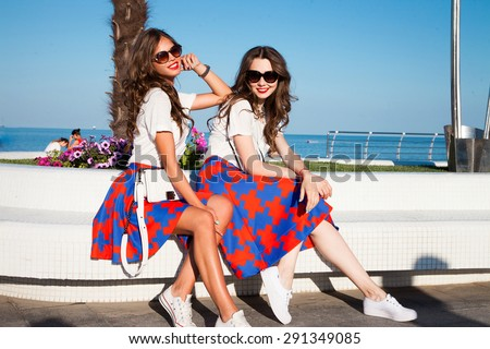 Young stylish hipster girls walking at nice hot summer day, wearing vintage trendy outfit and sunglasses .Similar outfit,woman skirt,trendy girls,fashion girls,friends on the beach,party girls,friends - stock photo