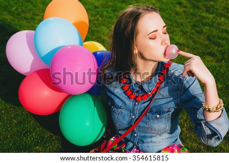 young stylish hipster teen girl happy, chewing bubblegum, sitting on grass in park, air balloons birthday party, cool accessories, colorful, having fun, denim shirt, fashion trend summer outfit - stock photo