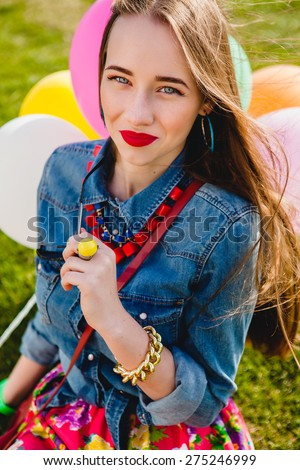 young stylish hipster teen girl happy smiling at park with air balloons birthday party, cool accessories, red lipstick makeup, colorful, summer sunny, have fun, sitting on grass, denim shirt - stock photo