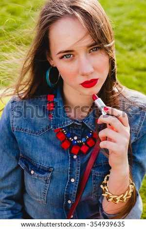 young stylish hipster teen girl, park party, cool accessories, red lipstick makeup, colorful, sunny, sitting on grass, denim shirt, fashion trend summer outfit - stock photo