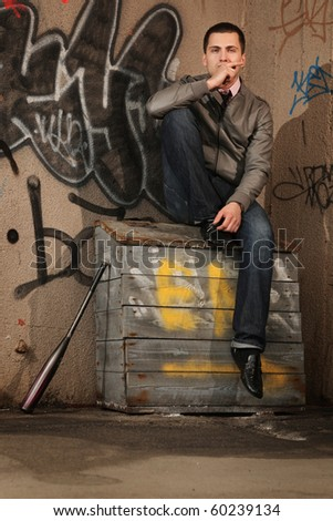 young stylish hooligan sitting in the sandbox - stock photo