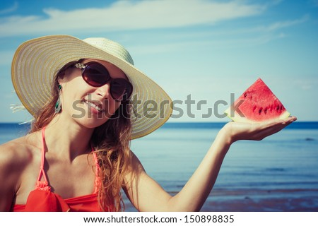 Young stylish lady in a hat and sunglasses at sea with watermelon