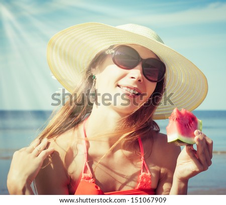 Young stylish lady in a hat and sunglasses at sea with watermelon - stock photo