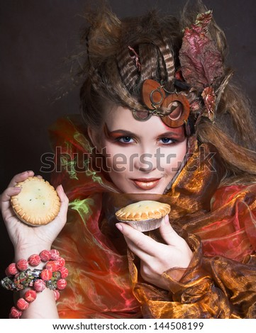 Young stylish lady with artistic make-up and autumn leafs in her hair and  with cake
